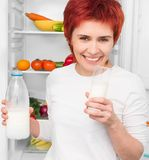 Woman against the refrigerator Royalty Free Stock Image