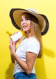 Young woman a bottle of sunblock. On a yellow background Royalty Free Stock Photo