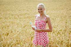 Young woman with bottle of water. Young attractive woman standing in a cornfield. she wears a plaid summer dress and holds a bottle of water in her hand Royalty Free Stock Images
