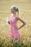 Young woman with bottle of water. Young attractive woman standing in a cornfield. she wears a plaid summer dress and holds a bottle of water in her hand Stock Images
