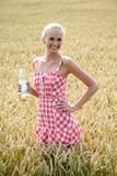 Young woman with bottle of water. Young attractive woman standing in a cornfield. she wears a plaid summer dress and holds a bottle of water in her hand Stock Photography