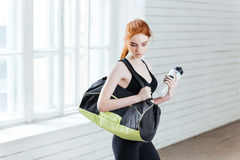 Young woman with bottle of water and sports bag Stock Images