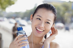 Young Woman with Bottled Water Listening to Music Stock Photography