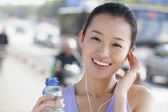 Young Woman with Bottled Water Listening to Music Royalty Free Stock Image