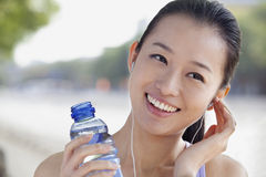 Young Woman with Bottled Water Listening to Music Royalty Free Stock Photography
