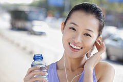 Young Woman with Bottled Water Listening to Music Stock Photo