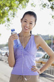 Young Woman with Bottled Water Listening to Music Royalty Free Stock Photo