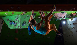 Young woman bouldering along ceiling of climbing gym Stock Photos