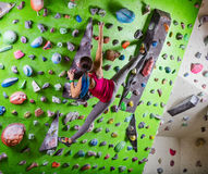 Young woman bouldering on climbing gym Stock Image