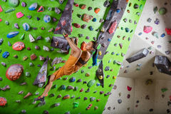 Young woman bouldering in climbing gym Stock Photography