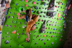 Young woman bouldering in climbing gym Royalty Free Stock Images