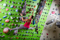 Young woman bouldering in climbing gym Royalty Free Stock Photo