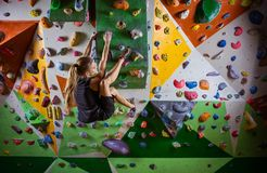 Young woman bouldering on overhanging wall in climbing gym. Young woman bouldering on overhanging wall in indoor climbing gym Royalty Free Stock Images
