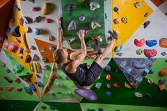 Young woman bouldering on overhanging wall in climbing gym. Young woman bouldering on overhanging wall in indoor climbing gym Stock Images