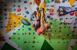 Young woman bouldering on overhanging wall in climbing gym. Young woman bouldering on overhanging wall in indoor climbing gym, making challenging move to reach Royalty Free Stock Image