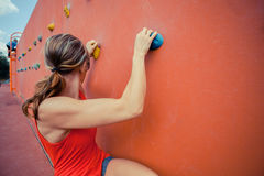 Young woman bouldering. A young woman is scaling a bouldering wall Royalty Free Stock Image