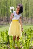 Young woman with a bouquet of daffodils in nature Royalty Free Stock Photos