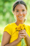 Young woman in with bouquet of dandelions Stock Images