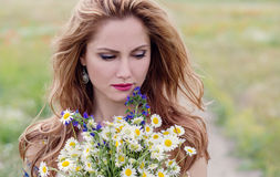 Young woman with a bouquet of field daisies Stock Photography