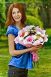 Young woman with bouquet of flowers. Red-haired smiling beautiful young woman in blue blouse with bouquet of flowers, against green of summer park Royalty Free Stock Image