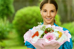 Young woman with bouquet of flowers Stock Photography