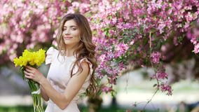 Young woman with bouquet of tulips. Young handsome woman with bouquet of tulips among flowering garden stock video