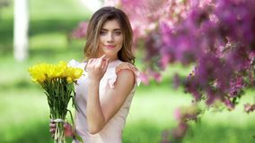 Young woman with bouquet of tulips. Young handsome woman with bouquet of tulips among flowering garden stock footage