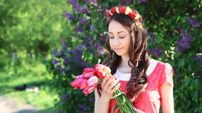 Young woman with a bouquet of tulips at the park in spring stock footage