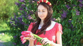 Young woman with a bouquet of tulips at the park in spring stock video