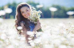 A young woman with a bouquet of white daisies on a meadow Royalty Free Stock Images