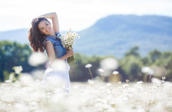 A young woman with a bouquet of white daisies on a meadow Royalty Free Stock Image