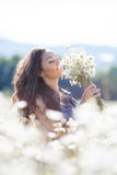 A young woman with a bouquet of white daisies on a meadow Royalty Free Stock Photos