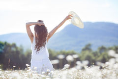 A young woman with a bouquet of white daisies on a meadow royalty free stock photography