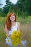 Young woman with bouquet of wild flowers Stock Photo