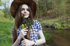 Young woman with bouquet of wild flowers. In the forest Stock Image