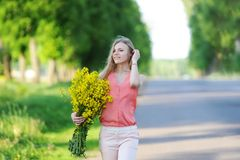 Young woman with bouquet of yellow colors walks on the country road royalty free stock photos