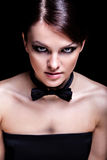 Young woman with bow tie. Portrait of young beautiful girl wearing smoking bow-tie against black background Royalty Free Stock Image