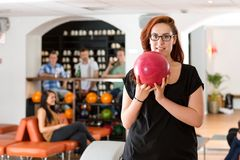 Young Woman Bowling in Club Stock Image