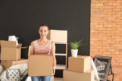 Young woman with box indoors. Moving into new house stock image