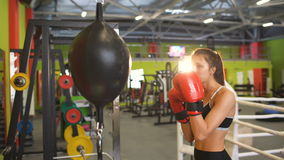 Young woman boxer hit punching bag during pre-match warm-up with her trainer in boxing club. Young woman boxer hit punching bag during pre-match warm-up in stock footage
