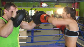 Young woman boxer training pre-match warm-up in the boxing ring with her trainer. In box club stock video