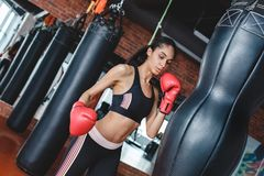 Young woman in boxing gloves in gym standing breathing before kicking punching bag royalty free stock images