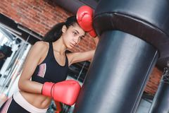 Young woman in boxing gloves in gym standing leaning on punching bag wiping off sweat tired stock photography