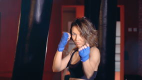 A young woman in boxing stance invites for a match.