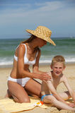 Young woman and boy at the beach. Young mother with a straw hat applying sun cream on her son's back Stock Photography