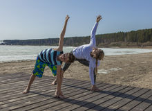 Young woman and boy doing Extended side angle pose. Royalty Free Stock Photography