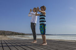 Young woman and boy doing Salutation to the Sun Royalty Free Stock Image