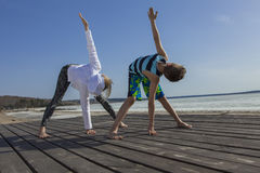 Young woman and boy doing wide legged bend on the beach Royalty Free Stock Photos