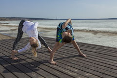 Young woman and boy doing wide legged Forward Bend, twist variation. Stock Photos