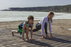 Young woman and boy doing yoga on the beach. Royalty Free Stock Images